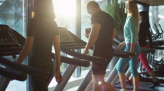 Young athletic man is using smartphone while exercising and running on treadmill - stock footage