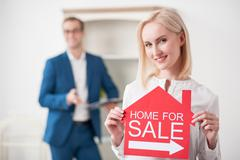 Cheerful young woman is presenting her house - stock photo