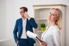 Attractive female realtor is working with a client - stock photo