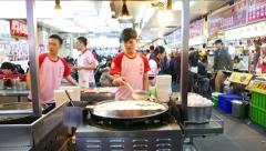 Young man cook oyster omelette at large round pan, food court kitchen, sound Stock Footage