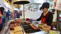 Making hot-dog with fresh sausage, food court at Shilin market Stock Footage