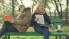 Irritated students having problem with homework and throwing notes in the park - stock footage