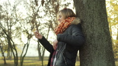 Girl leaning on tree in the autumnal park and playing with maple leaf Stock Footage