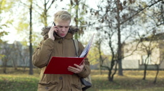 Boy talking on cellphone and holding red binder in the autumnal park Stock Footage