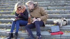 Students sitting on the stairs and doing homework together Stock Footage