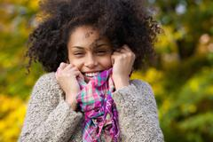 Young woman laughing outdoors in autumn - stock photo
