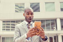 Closeup portrait anxious young business man looking at smart phone seeing bad - stock photo