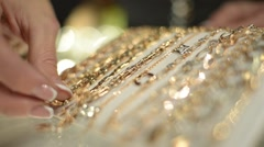 Jewels Market - the seller shows gold jewelry earrings, rings, bracelets, chain - stock footage