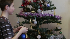 Teen dresses up Christmas tree at home Stock Footage