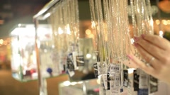 Market jewels - the seller shows silver jewelry chains - stock footage