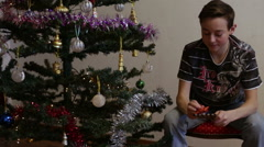 Teen opening Christmas gift near Christmas tree - stock footage