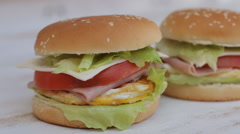 Juicy hamburgers with fresh vegetables and bacon, Close up Stock Footage