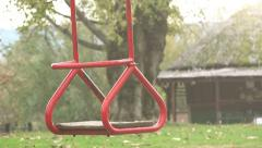Empty red swing seat swaying in park playground Stock Footage