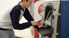 Teenager boy insert credit card in cash machine Stock Footage