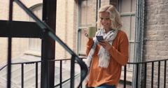 Beautiful  blonde woman using smart phone outside drinking coffee on a break - stock footage