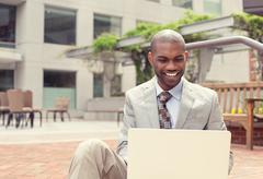 happy businessman working on laptop computer outdoors - stock photo
