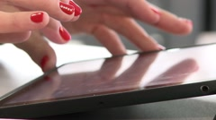 Women's hands with bright red nail Polish work on the tablet.  Stock Footage