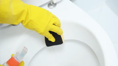 Hands on yellow gloves cleaning a WC - stock footage