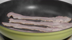 Pan frying Bacon on the stove top - stock footage