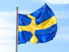 Flag of Sweden waving against blue sky - stock photo