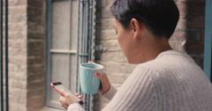 Beautiful asian woman using smart phone outside drinking coffee on a break - stock footage