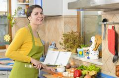 Beautiful smiling woman preparing fresh meal - stock photo