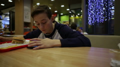 Teen Eating Hamburger and play in Smartphone - stock footage