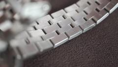 Polished steel watch wristlet being placed on a brown surface - stock footage