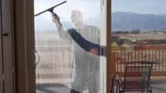 Man cleaning the large house windows during the day Stock Footage
