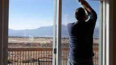 Man cleans his house windows during the day Stock Footage