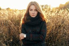 Noon portrait of serious young beautiful redhead woman cold season outdoors - stock photo