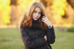 Outdoors portrait of young beautiful redhead woman autumn background - stock photo