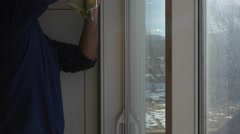 Man cleans house windows during the day Stock Footage