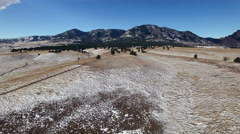 Aerial drone fly winter snowy dusted fields to mountain backdrop. Stock Footage
