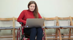 Disappointed disabled woman using laptop while sitting wheelchair in office Stock Footage