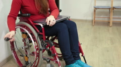 Unrecognizable paralyzed woman trying to insert power plug in wall outlet Stock Footage