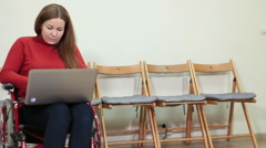 Young Caucasian disabled woman using laptop while sitting in wheelchair in room Stock Footage