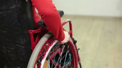Caucasian young woman sitting in invalid chair indoor and rolling wheel by hand Stock Footage