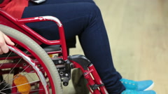 Disabled person turning his wheel chair with hand in room, close up view Stock Footage