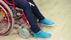 Caucasian female trying to put her legs wearing blue shoes on the wheelchair Stock Footage