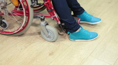 Paralyzed person putting his legs by hands on the step of wheel-chair Stock Footage