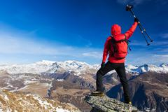 Rear view of a hiker that shows enthusiasm raising his arms. Concepts: victor Stock Photos