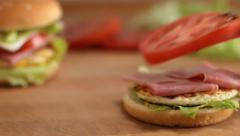Preparing a cheeseburger with lettuce, egg, bacon, tomato and cheese.Close up Stock Footage