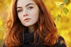 Young beautiful redhead woman in scarf and plaid jacket autumn outdoors - stock photo