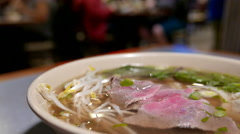 People eating Pho inside Vietnamese noodle house - stock footage