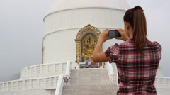 Woman takes a picture of a Stupa on a mobile phone Stock Footage