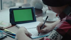 The freelancer works in cafe using tablet with greenscreen Stock Footage