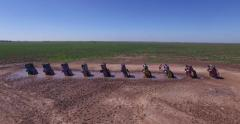 Aerial shot pushing toward and flying over Cadillac Ranch, public art Stock Footage