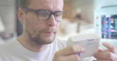 Stock Video Footage of Young Man is Reading a Prescription on a Box With Pills Attentively Takes the