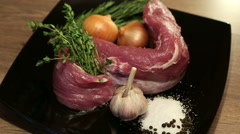 Raw pork meat with herbs, onion, garlic, salt, pepper close up rotation Stock Footage